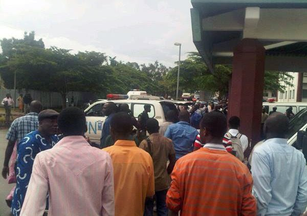 This citizen journalism photo acquired by the AP shows crowds of people outside the the National Hospital in Abuja, Nigeria as an ambulances arrive Friday Aug. 26, 2011 following a large explosion whi
