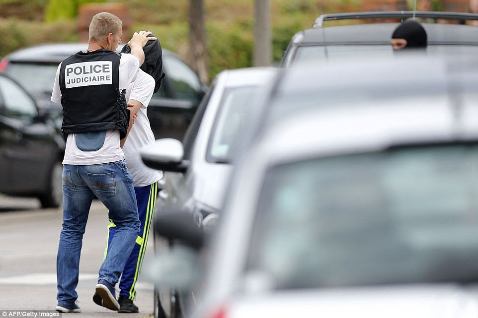 Apreensão: O homem foi retratado sendo empacotado em um carro da polícia depois de um ataque a uma casa na cidade de Saint-Etienne-du-Rouvray