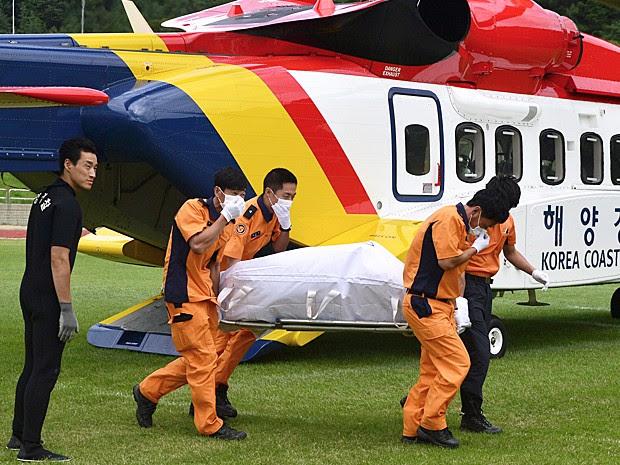 Resgatistas carregam o corpo de uma das vítimas do naufrágio do pesqueiro na Coreia do Sul (Foto: Ryu Hyung-geun/Newsis via AP)