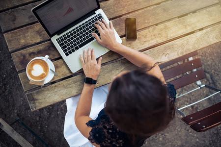 au téléphone: Vue du haut de femme en utilisant son ordinateur portable dans un café. Vue aérienne de la jeune femme assise à une table avec une tasse de café et de téléphone mobile surfer sur le net sur son ordinateur portable. Banque d