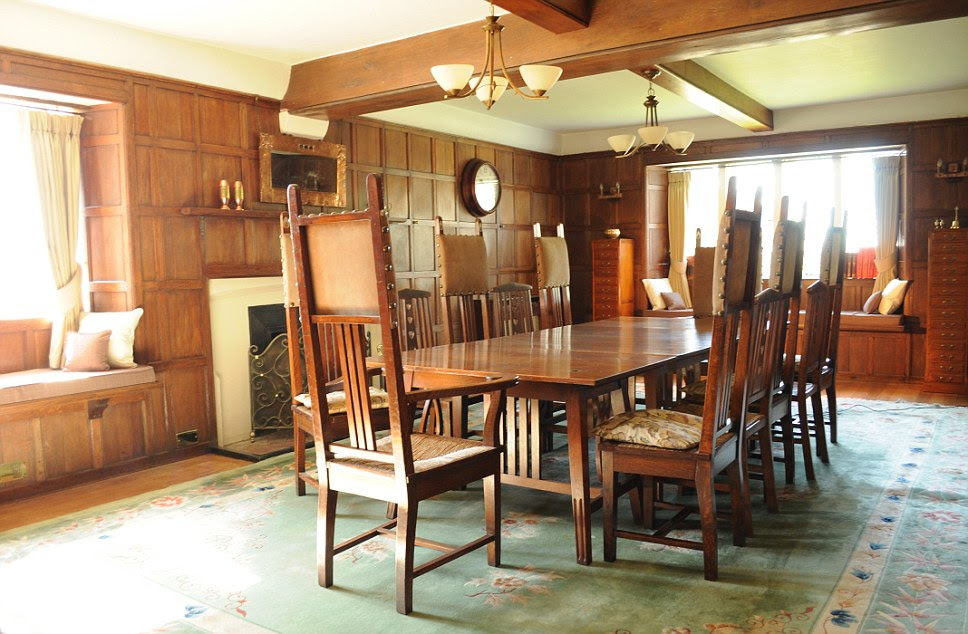 Wooden paneling and beams give the dining room at Happisburgh Manor an airy light feel, while the giant rug adds decadence