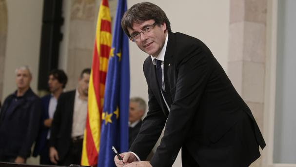 Catalan regional President Carles Puigdemont signs an independence declaration document after a parliamentary session in Barcelona (AP Photo/Manu Fernandez)