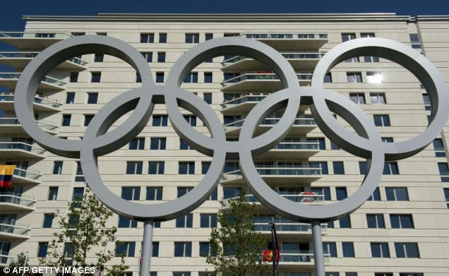 A giant set of Olympic rings stands in the Olympic village