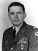 Head and shoulders of a white man with dark hair wearing a military jacket with a round patch on the upper sleeve, and oak leaf emblem atop the shoulder, and ribbon bars and pins on the left breast.