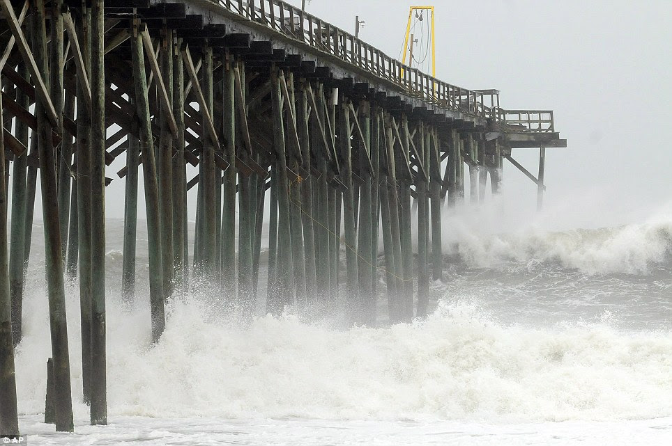 Waves pound Carolina Beach pier in Carolina Beach, North Carolina as Hurricane Sandy makes its way up the Atlantic coast of the U.S.
