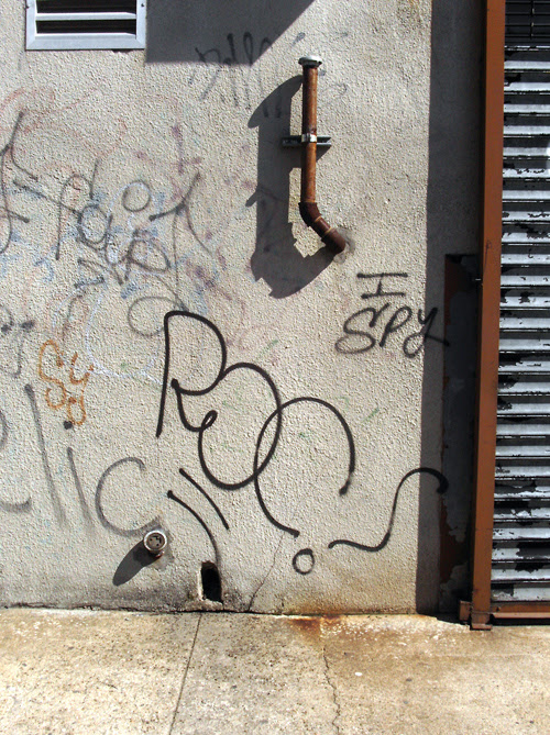 Graffiti with vent, pipe,  sidewalk, and more
