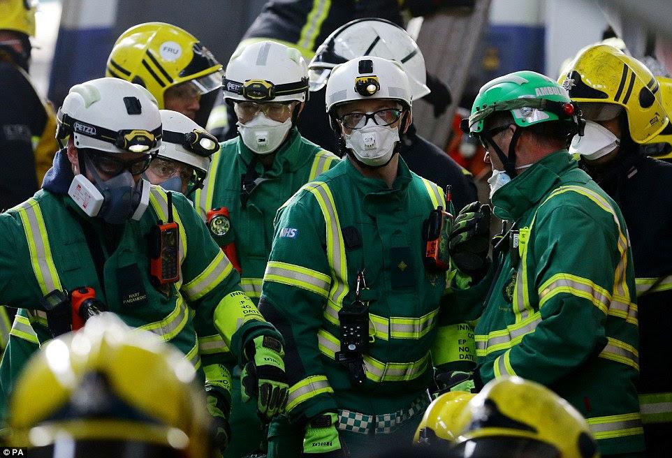 Στιγμές μακριά: Παραϊατρικό ήταν μάσκες σκόνης να προστατεύσουν τον εαυτό τους καθώς τείνουν σε εκείνους που εμπλέκονται στην σταδιακή καταστροφή