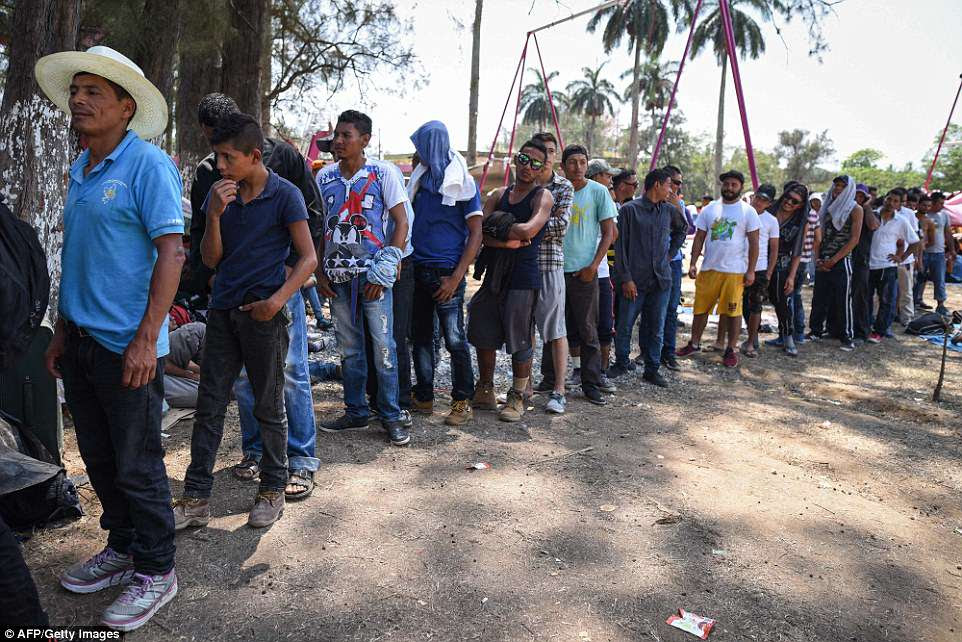 "Central Americans -taking part in a caravan called ""Migrant Viacrucis""- wait in line to get a meal in Matias Romero, Oaxaca state"