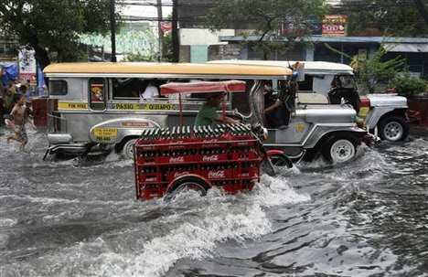 Motorists drive through floodwaters following a sudden downpour that inundated low-lying areas in Manila, Philippines  Tuesday May 24, 2011.