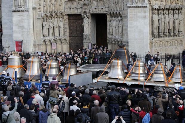 Turistas e curiosos acompanham a chegada dos sinos na Notre Dame (Foto: Christophe Ena/AP)