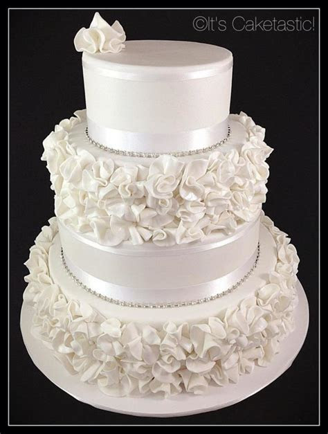 A Four Tier Wedding Cake With Ruffle Flowers Inside There