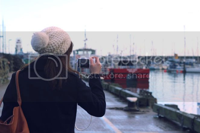 girl taking photo of boats