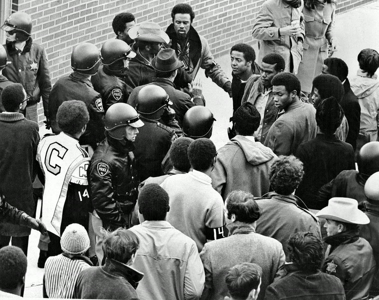 Description of  NOV 2 1969 - Disturbance Mars CSU Football Game. Several helmeted Colorado State University policemen try to break up a ruckus beneath the stands at CSU's Hughes Field during halftime of the CSU-University of Texas at El Paso football game Saturday. A few fistfights and scuffles broke out in arguments over the dismissal of 14 black athletes at the University of Wyoming. Two of the persons in the incident wear black armbands number 14, symbolic of groups supporting dropped gridders. (Barry Staver/The Denver Post)
