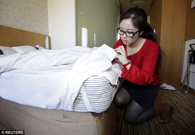 Zhuang examines the mattresses for their structure and cleanliness during her hotel stay
