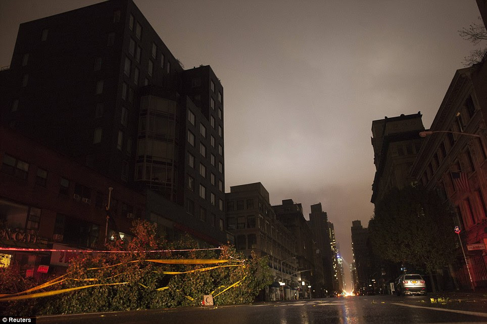 Downed: A fallen tree lays along a darkened Sixth Avenue in Chelsea during a blackout caused by rising river waters as Hurricane Sandy made its approach in New York