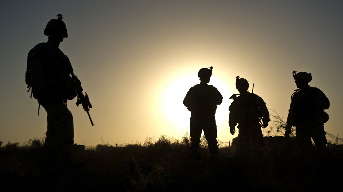 "U.S. soldiers stand at a checkpoint around Lakokhel camp in Afghanistan in 2010. Many soldiers return from war suffering from ""moral injuries,"" or dealing with the fact that their sense that right and wrong was violated."