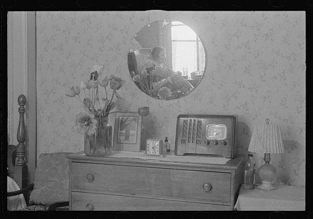 Washington, D.C. A corner of a bedroom, probably in a rooming house for government clerks, showing reflected in a round mirror above a dresser a woman doing handwork