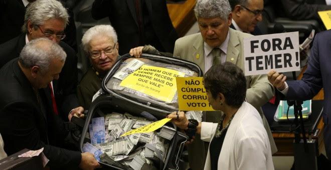 Diputados de la oposición en la cámara baja del Congreso brasileño levatan una maleta con dinero falso antes de la votación en la que se rechazó que el Tribunal Supremo juzgue al presidente Temer por corrupción /REUTERS (Adriano Machado)
