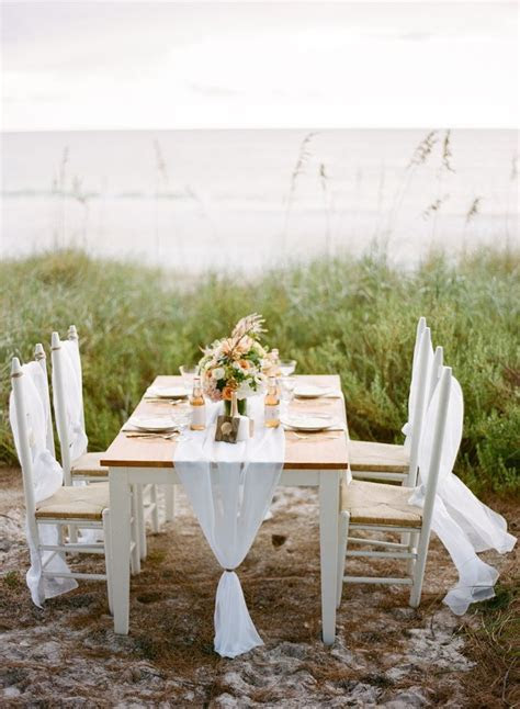 Simple wedding reception table setting on the beach   Fab