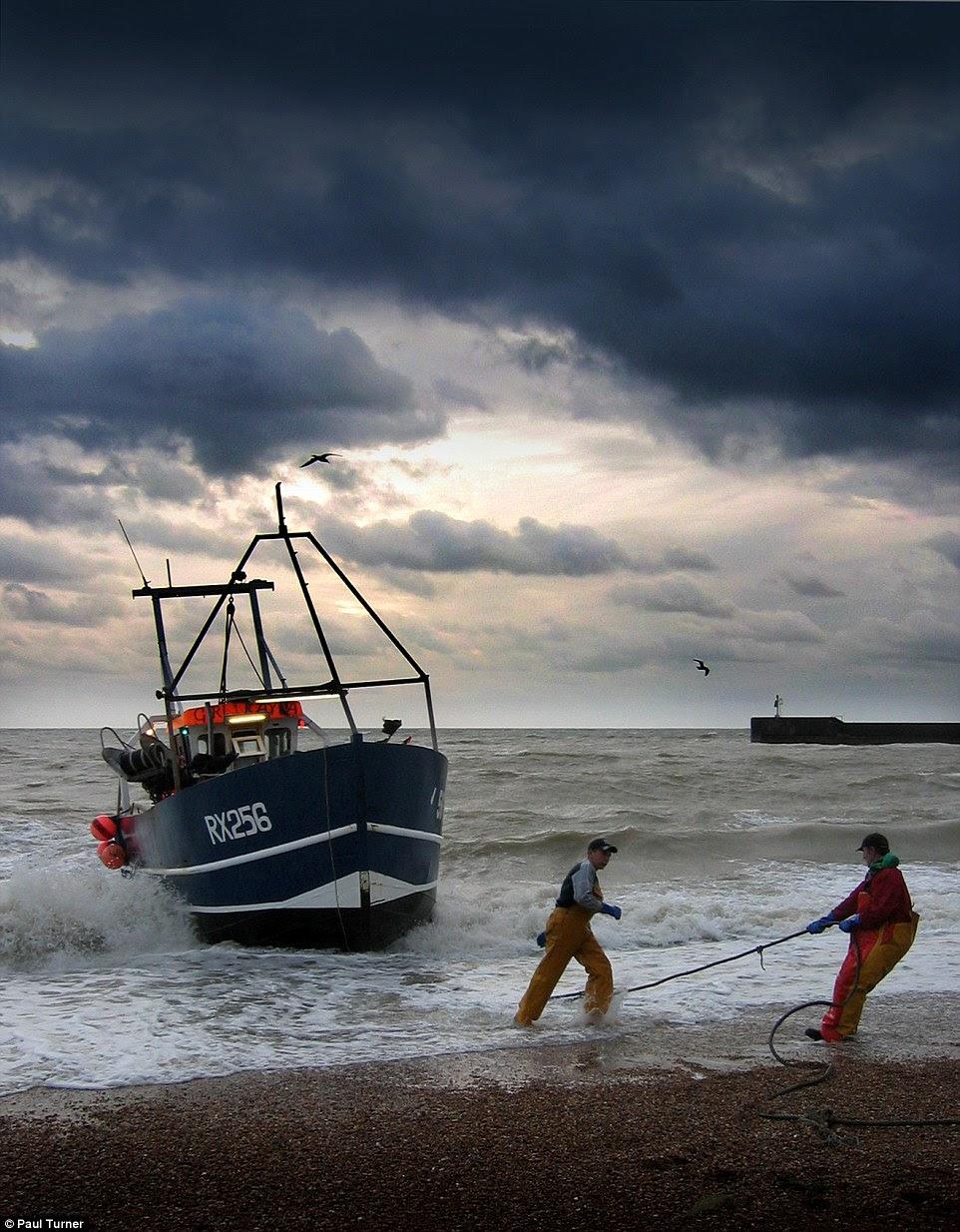 Fisherman arrastar sua embarcação para a praia nesta imagem apropriadamente chamado, que vem em terra por Paul Turner fotografado em Hastings, East Sussex