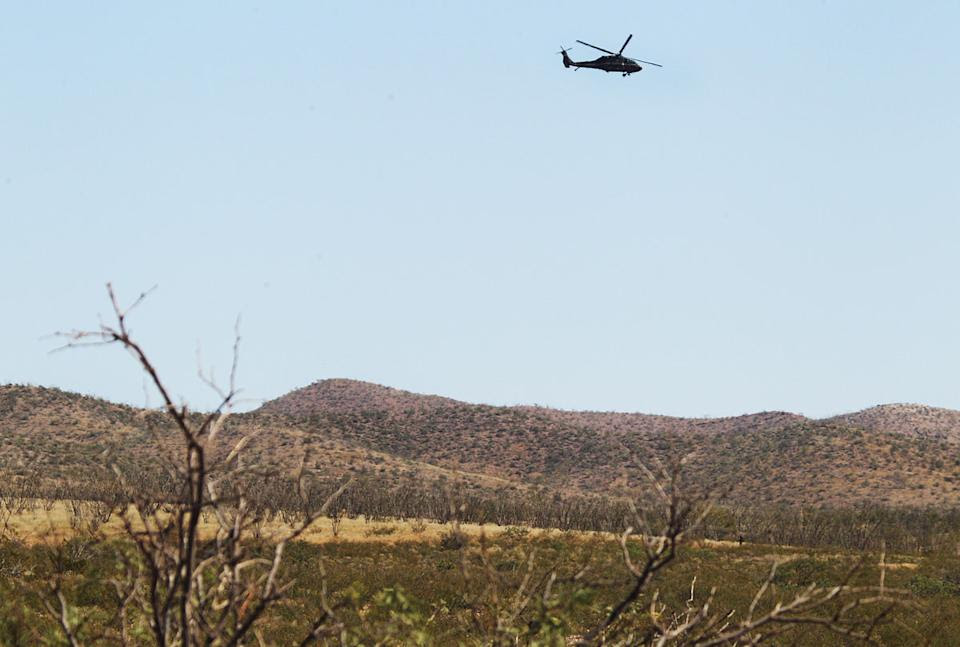 A U.S. Customs and Border Protection helicopter flies overhead near the scene where a Border Patrol agent was killed early Tuesday, Oct. 2, 2012, near...