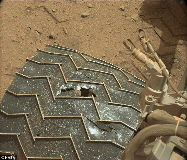 A large hole has been spotted (shown) in the middle-right wheel of Nasa's Curiosity rover on Mars. The dent is the latest in several bumps and bruises the rover has experienced on the red planet, which has surprised engineers. It is not a problem for now but could become one if the hole grows in size