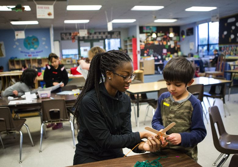 Staff member Adwoa Asare-Konadu works with RJ Gupte, 6, on a God's Eye, or Ojo de Dios, during craft time at Kids Co. (Lindsey Wasson/The Seattle Times)