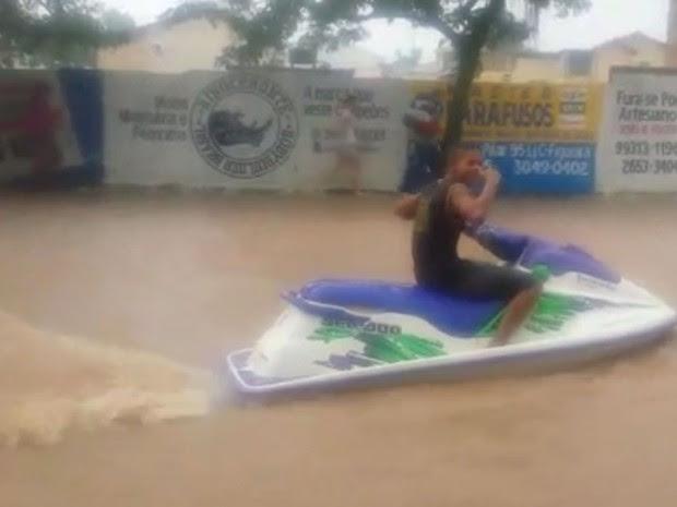 Homem foi flagrado andando de moto aquática no meio de um alagamento em Duque de Caxias (Foto: Reprodução/ TV Globo)