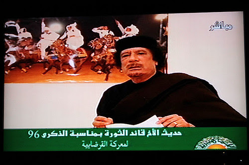 Poster Libyan revolutionary leader Muammar Gaddafi speaking on television in the North African oil-rich state. Libya has fought off an imperialist onslaught for the last eight months. by Pan-African News Wire File Photos