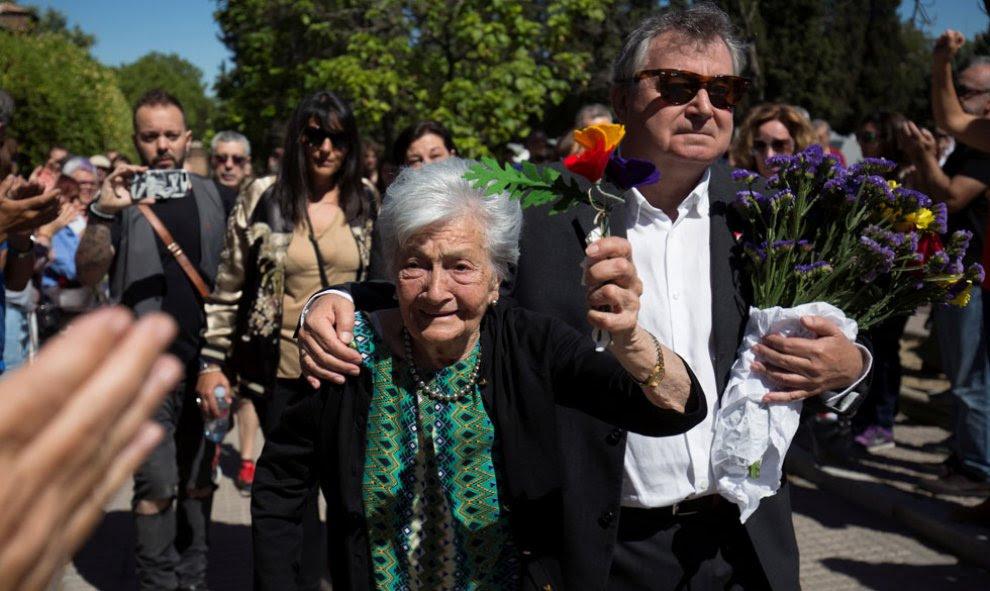 La lucha de una vida. Ascensión levanta unas flores con los colores republicanos junto a su hijo.- REUTERS