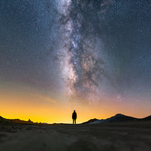 a photo of the Milky Way seen from a dark desert. The dusty colors light up the sky.