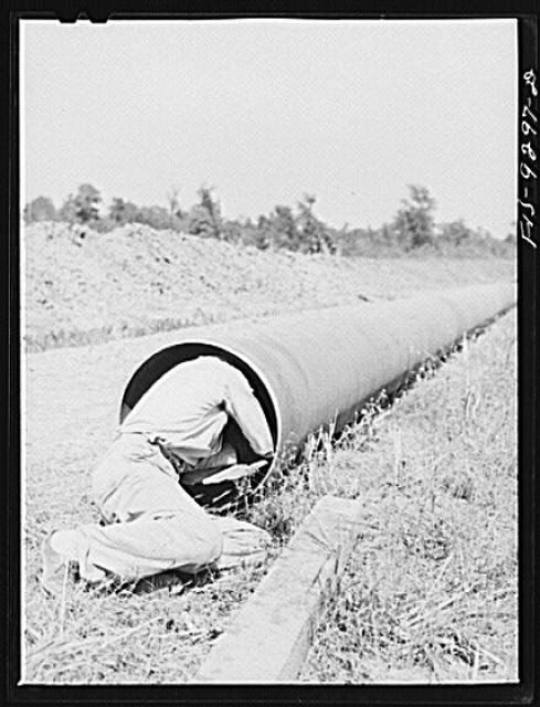 Arkansas-Texas state line to Gurdon, Arkansas. War emergency pipeline from Longview, Texas to Norris City, Illinois. Worker cleaning out any dirt that may be inside the pipe by sliding through sections of pipe before they are welded to main stem
