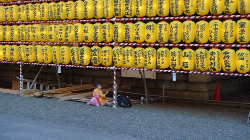 Little girl eating alone during Mitaka Matsuri