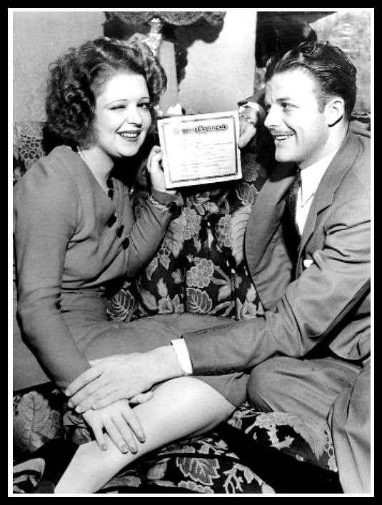 Clara Bow and husband Rex Bell in 1931 holding their marriage certificate