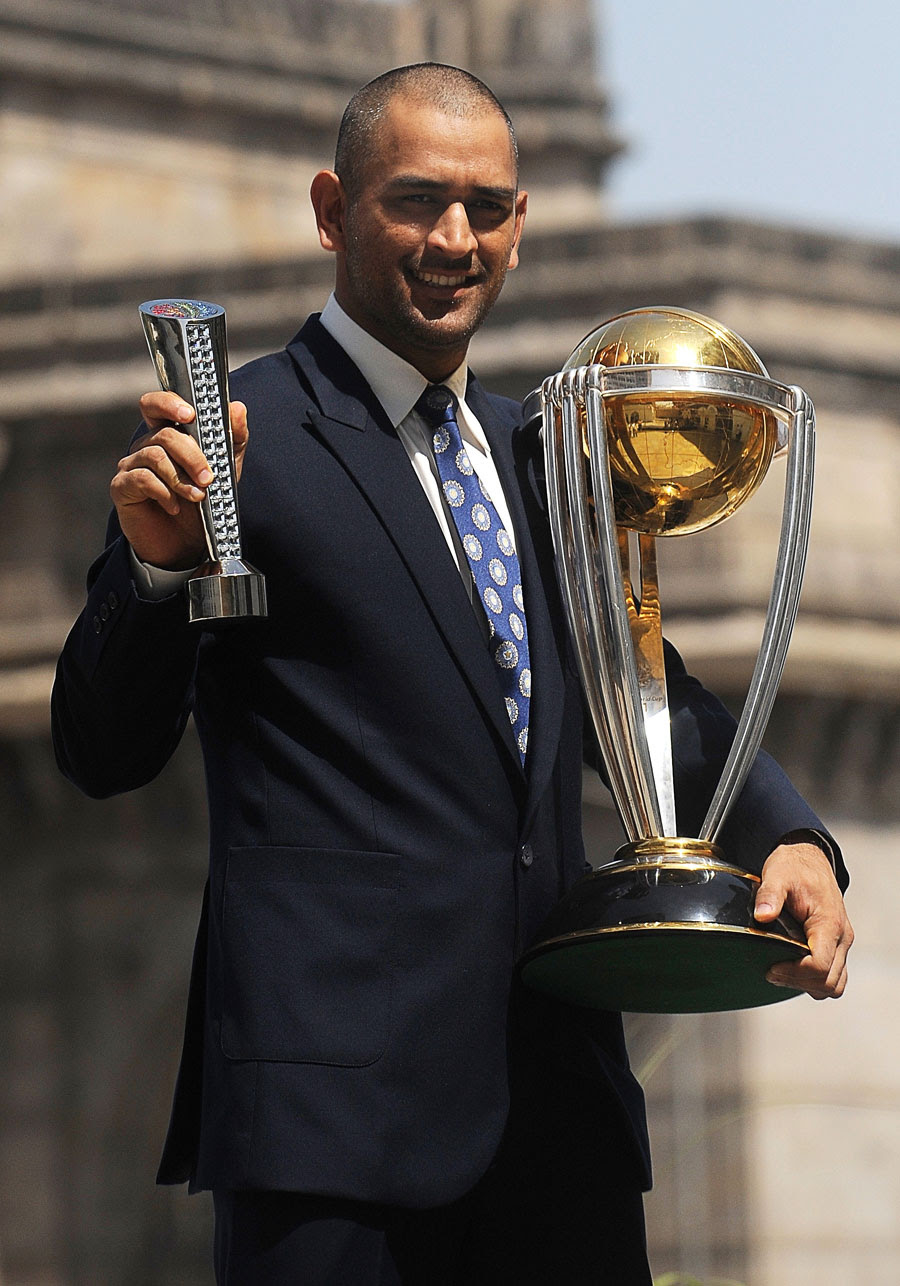 MS Dhoni with the World Cup trophy and his Man of the Match award from the final