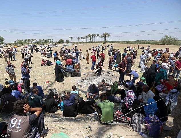 Exodus: The desperate Iraqi families (pictured) who fled Islamic State's violent attack on Ramadi are now stuck in a deadly no man's land between the city and Baghdad, where they are being refused entry