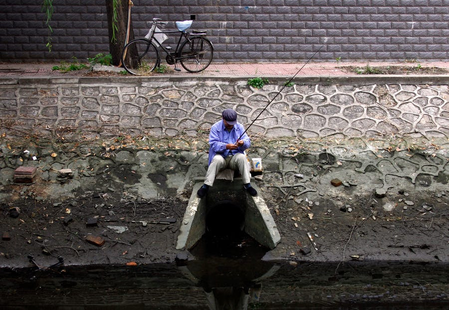 A fisherman sits on top of a drain at a polluted canal in central Beijing.