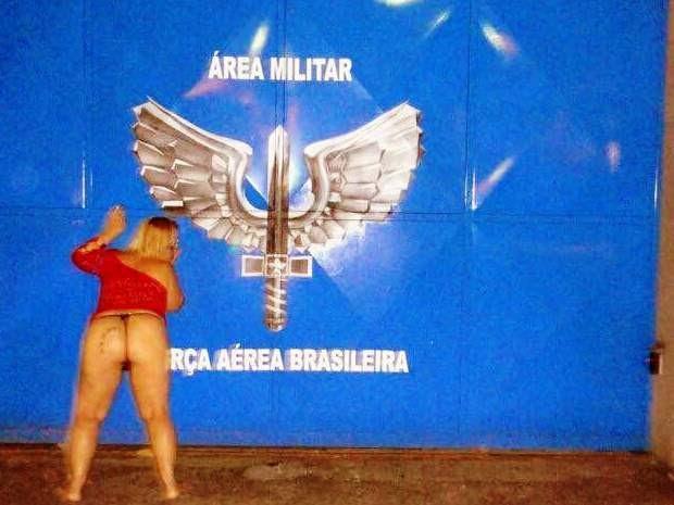 Mulher tem fotos com símbolos militares ao fundo (Foto: Reprodução/Facebook)