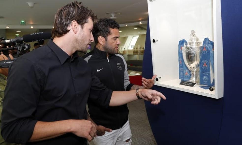 Maxwell mostra a Daniel Alves troféu na sede do Paris Saint-Germain (Foto: Reprodução do site oficial do Paris Saint-Germain)