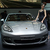 A woman poses with a Porsche Turbo