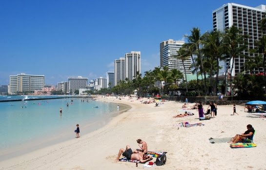 In this Monday, March 13, 2017 photo, people relax on the beach in Waikiki in Honolulu. (AP Photo/Caleb Jones)