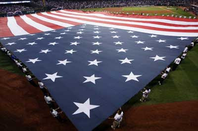 An American flag is unfurled in the outfield before the start of Game 3 of Major League Baseball's ALCS playoff series between the Cleveland Indians and the Boston Red Sox in Cleveland.