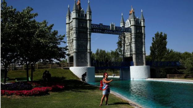 A woman taking a selfie in front of a replica of London's Tower Bridge