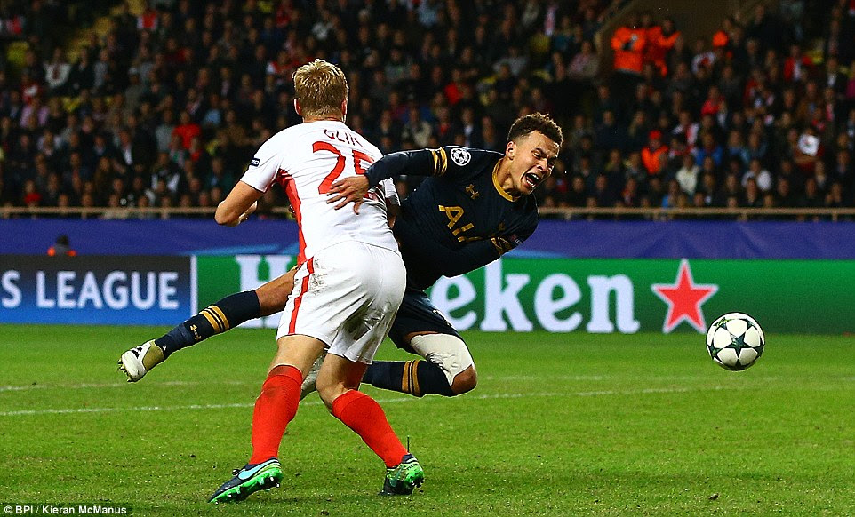 Dele Alli is fouled by Kamil Glik as he looks to turn away from the Monaco defender to earn Tottenham a second-half penalty
