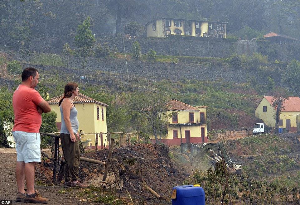 Um casal olhar para as casas evisceradas nos arredores de Funchal, capital da Ilha da Madeira, em Portugal.  Mais de 1.000 turistas foram evacuados como incêndios ameaçam resorts na ilha