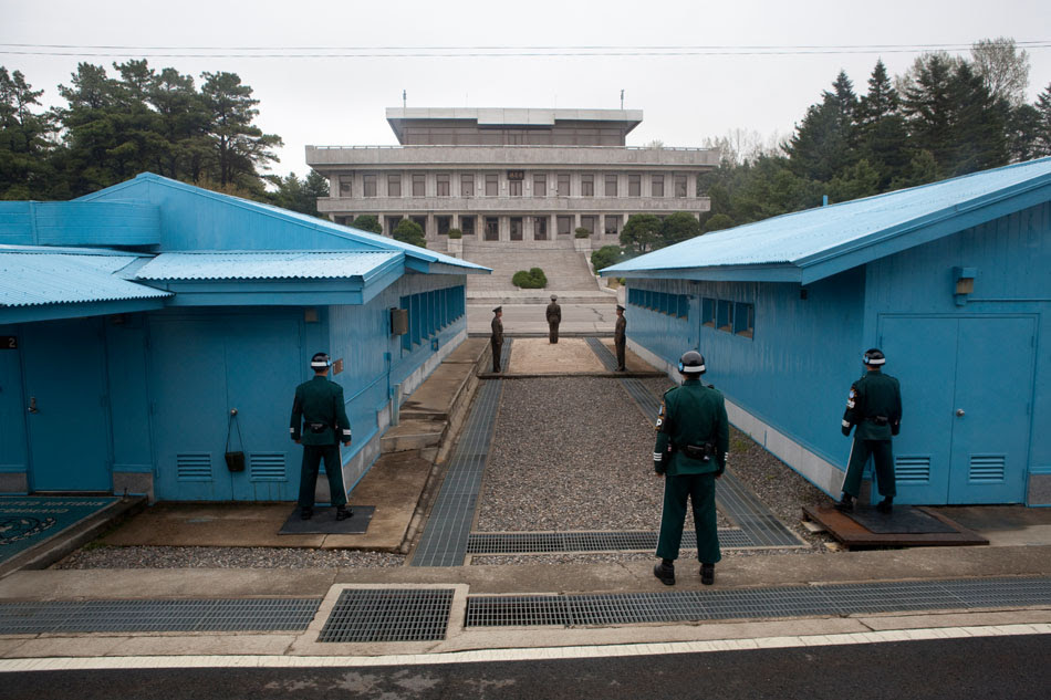 The North Korean guards, in grey uniforms, stand off at the Military Demarcation Line marked by the conrete strip at their feet. The South Korean gaurds, in blue, always stand half exposed behind the conference rooms in case of attack.