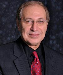 Portraid of Dr. Mazen E. Hamad wearing a black suit and a red tie against a black backdrop