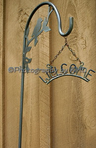 a wrought iron welcome sign hanging by a chain