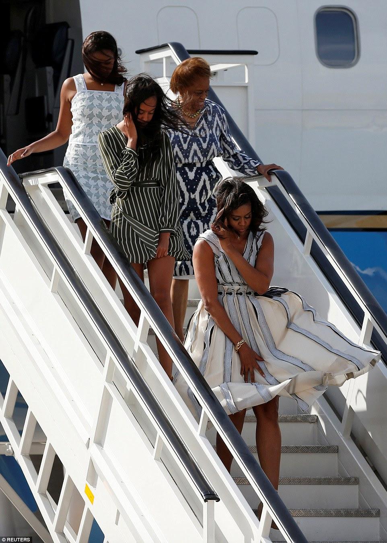 As mulheres Obama - viajando com a mãe de Michelle Marian Robinson - tudo equilibrado segurando seus cabelos e seus vestidos para baixo no vento