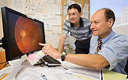 Epidemiólogo Chung-Jung Chiu (izquierda) y bioquímico Allen Taylor  examinan una imagen de la retina de un paciente que tiene la  degeneración macular. Enlace a la información en inglés sobre la foto